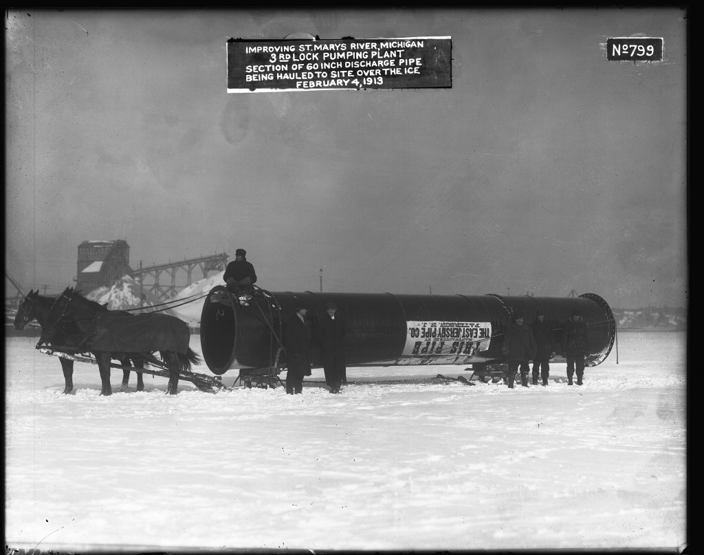 """Two horses pulling a 60 inch pipe across snow. The man holding the reins sits atop the pipe itself, while five other men (two of them in long winter coats, the other three dressed warmly and probably workers) stand next to the pipe facing the camera. A label on the pipe, upside down, reads: This pipe manufactured by the East Jersey Pipe Co. Paterson N.J. [New Jersey]."""""""
