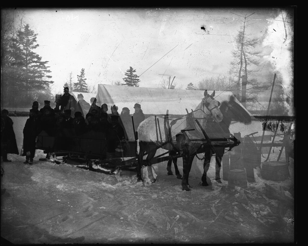 A double exposed photograph shows an eerie view of a group of men at camp overlaid by a transparent horse-drawn sleigh.