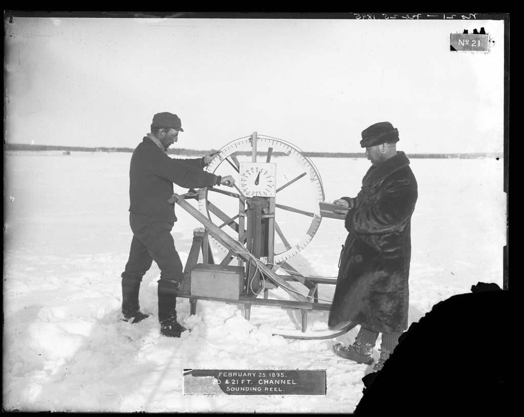 """Two men in fur coats and hats use a sounding reel on an iced-over, snow-covered channel. The label includes the date February 25, 1895, and caption """"20 & 21 ft. channel. Sounding Reel."""" Bottom right corner of original photograph is missing due to emulsion flaking."""