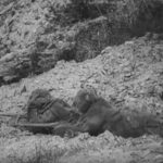 Two snipers in camouflage rock suits take up position in the film Flashes of Action.
