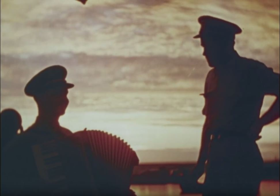 Two men in silhouette watch a sunset. The men are wearing military caps.