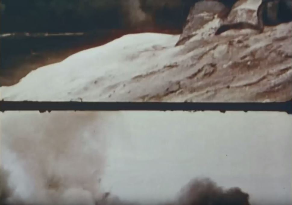 A still from The Battle of Midway shows the film going out of frame. A dark frameline is in the center of the image, along with smoke.