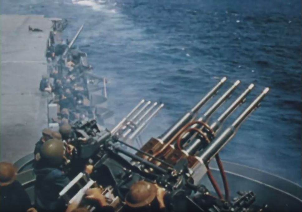 A row of guns are shown on the side of a ship, overlooking water.