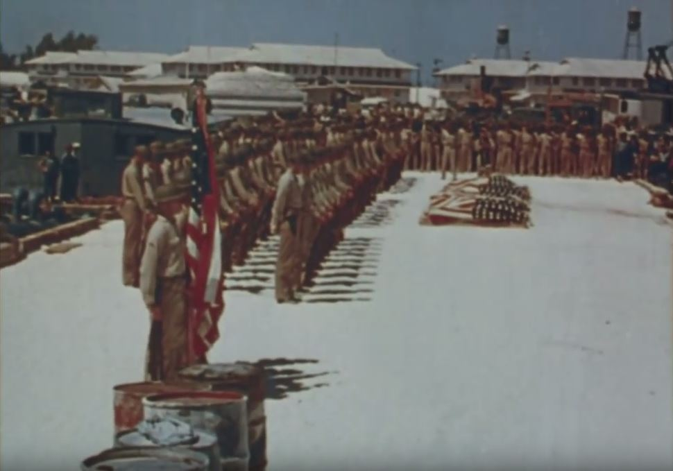 Sailors are lined up in front of the flag-wrapped coffins of their fallen. The men are wearing khaki uniforms.