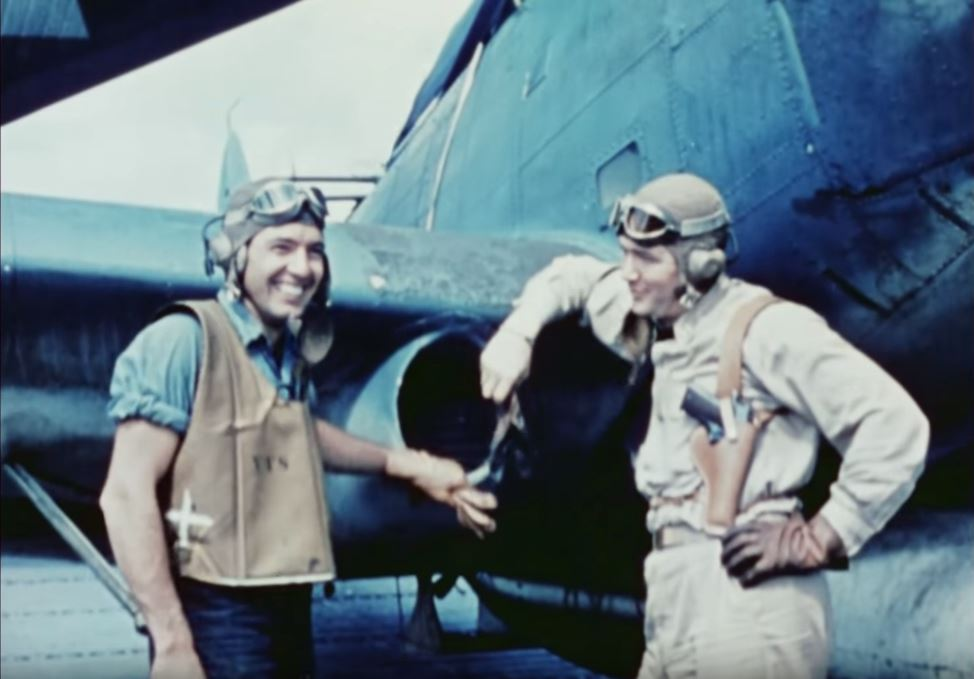 Two men pose in front of an airplane.