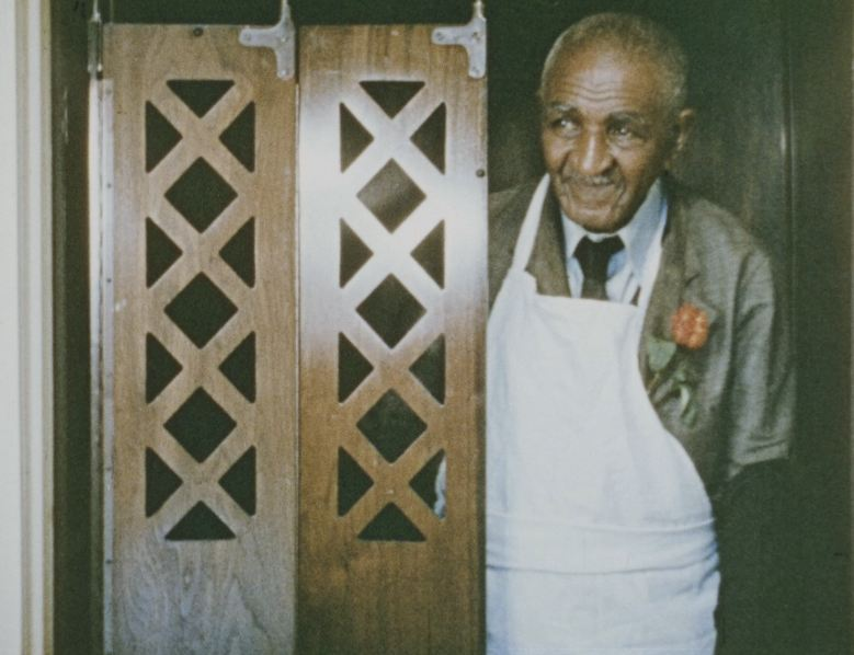George Washington Carver stands in an elevator.