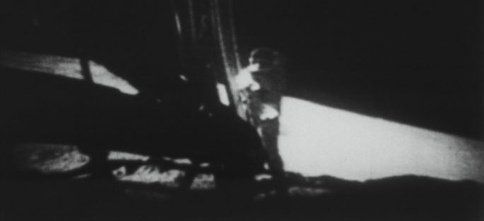 Astronaut standing on the ladder of the Apollo 11 lunar module.