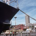 Two crewmen stand at the starboard bow of the guided missile cruiser USS LEAHY (CG-16), in port during the Seattle Sea Fair 1982. In the background, the Space Needle can be seen. Local Identifier: 330-CFD-DN-ST-83-01274 (https://catalog.archives.gov/id/6371844)