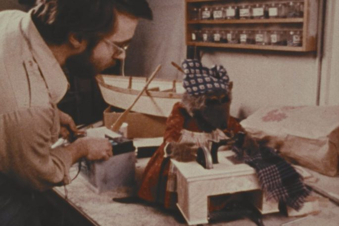 A puppeteer works inside the Muppet workshop. He adjusts radio controls next to a Hetty Muskrat puppet.