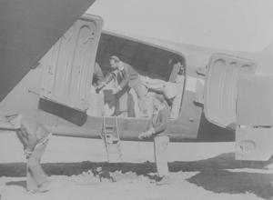 A man loads films onto a plane.