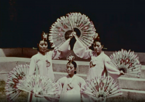 Korean women in traditional dress dancing with fans.