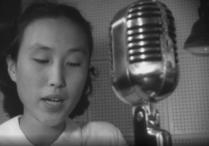 A woman speaking into a mircophone, broadcasting from Tokyo, Japan.