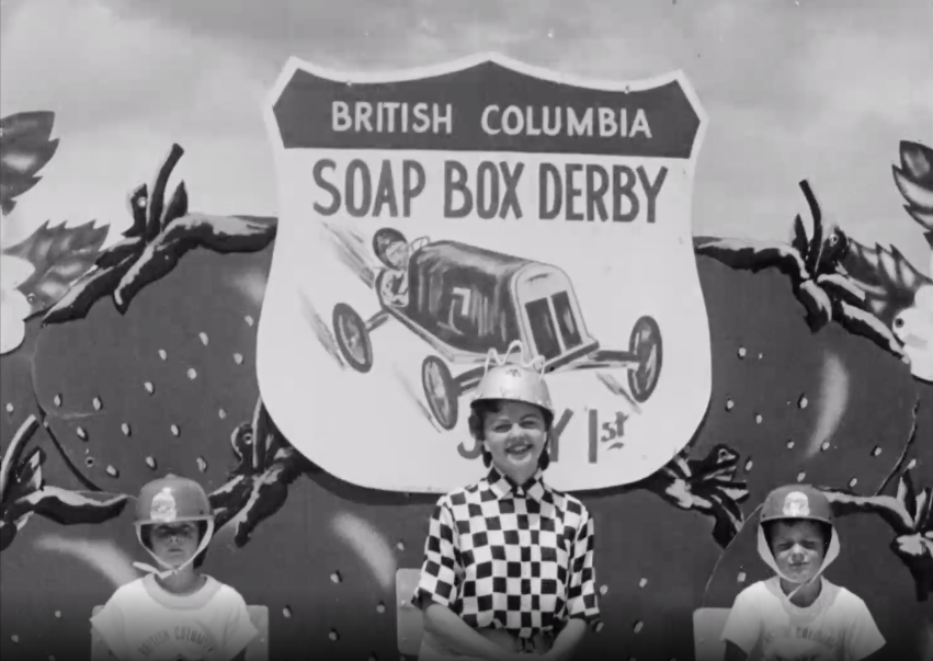 """A woman wearing a checked shirt and a metal bowl as a helmet is flanked by two children wearing helmets and t-shirts. A large sign behind them reads """"BRITISH COLUMBIA SOAP BOX DERBY."""""""