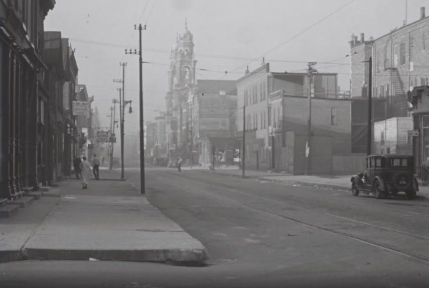 Street view. Streetcar tracks run down the center of the street, and a car is parked on one side. A church with two bell towers is in the background of the image.