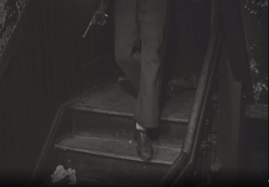 A man takes a step off a stairwell landing holding a gun in his right hand. There is trash on the stairs and the paint on the walls is peeling.