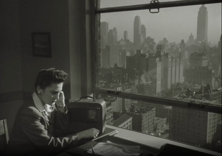 A woman sits in front of a window by a radio. The window shows a dense cityscape outside.