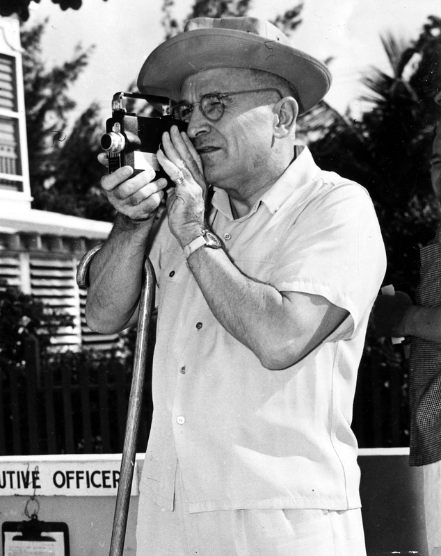 President Harry S. Truman holding a movie camera to his eye, a cane hooked over his arm..