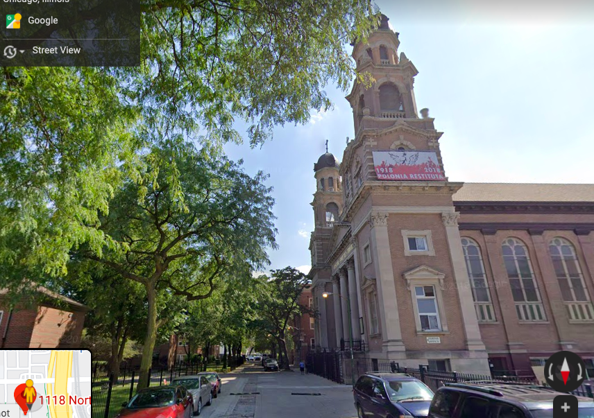 """Side view of a church with two bell spires. A banner reads """"1918 2018 POLONIA RESTITUTA."""" Cars line either side of the street."""