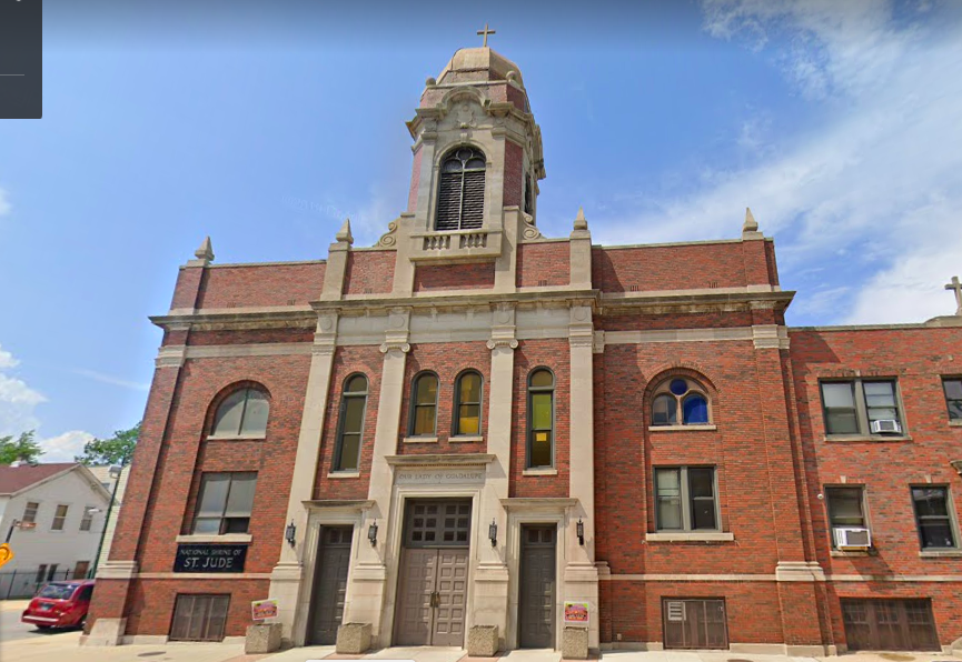 """A red brick building with a bell tower, topped by a cross. A sign on the left of the building reads """"National Shrine of St. Jude."""" Carved into the stone above the front door is """"Our Lady of Guadalupe"""""""