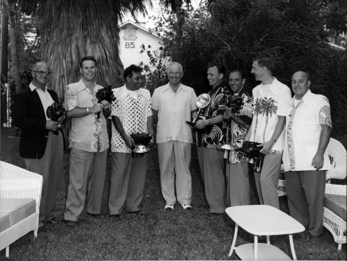 A group of men holding still and movie cameras poses around President Truman.