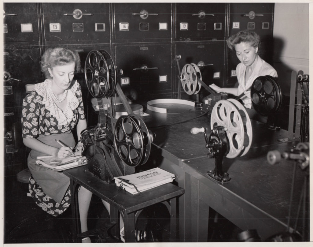 Two women inspect and view film while recording information in notebooks. The women are sitting at a table in front of large cabinets and are wearing dresses.