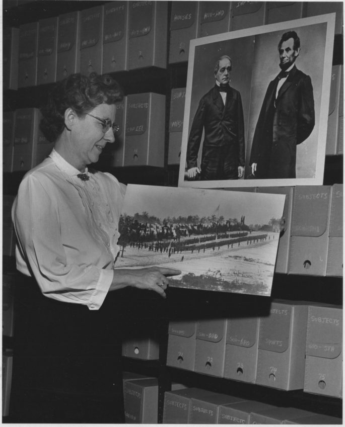 Photograph of Josephine Cobb inspecting a Mathew Brady photograph.
